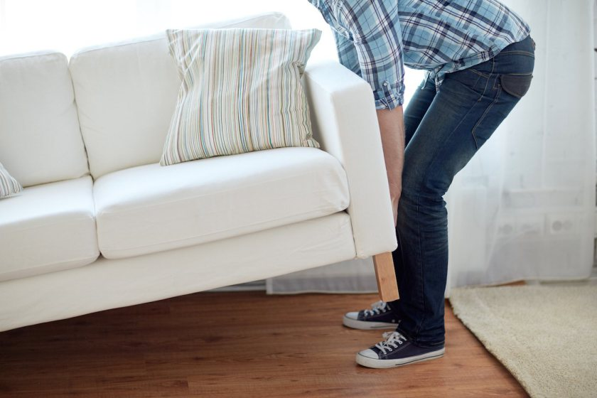 new home, real estate, moving and furniture concept - close up of male lifting up sofa or couch